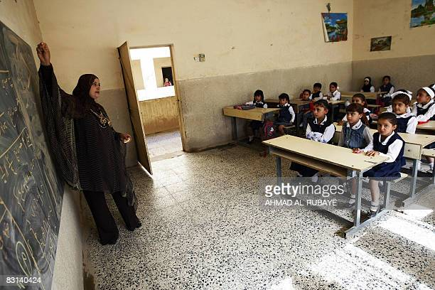 An Iraqi teacher writes on the blackboard as she leads a class on the first day of school after the end of the Islamic holy month of Ramadan and the...