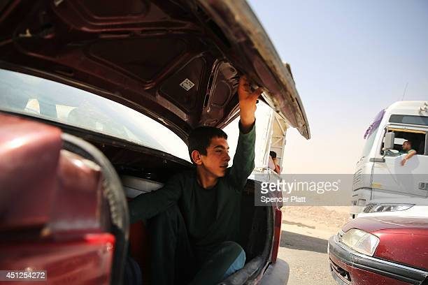 An Iraqi teen sits in the trunk of the family car as they wait to enter a temporary displacement camp for Iraqis caughtup in the fighting in and...