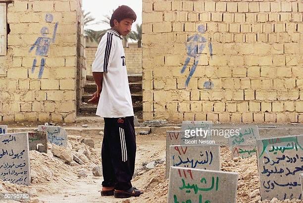 An Iraqi teenager mourns his 2 dead brothers amid graves in a soccer field converted to a cemetary in the flashpoint Iraqi city of Fallujah on May 03...