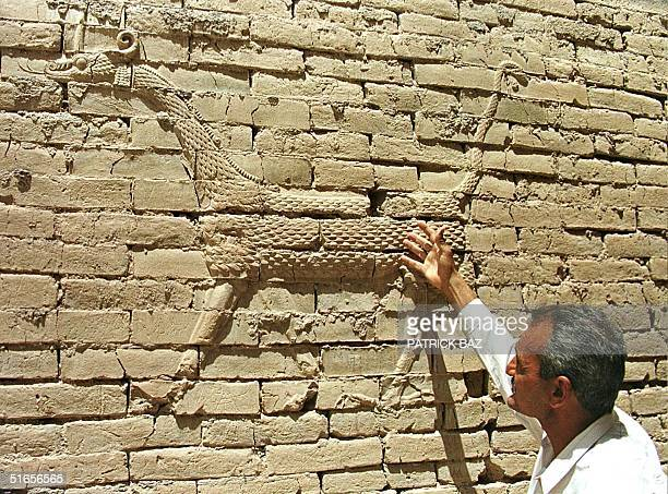 An Iraqi tour guide shows the Mushushu one of the symbols of the people of Babylon depicted on a wall of the ancient city's Ishtar gate 01 May 1999...