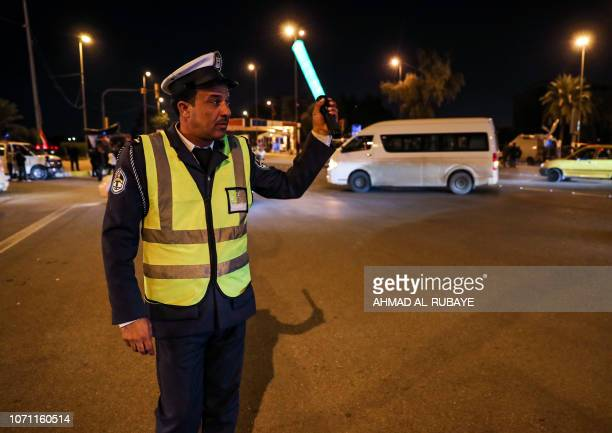 An Iraqi traffic policeman motions for cars to pass by in the capital Baghdad's highsecurity Green Zone where key government offices and Western...