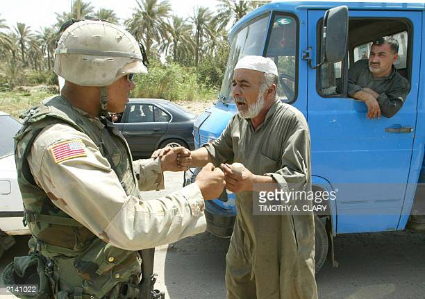 An Iraqi truck driver argues with a US soldier with the 1st Armoured Division at a roadblock near the AlMuthana Bridge in the Aazamiyah district of...