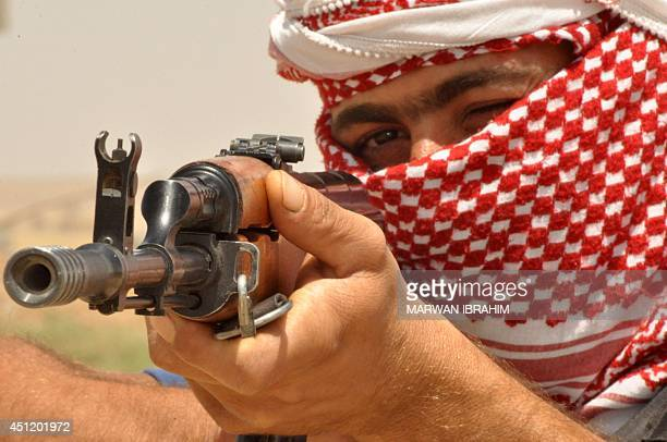 An Iraqi Turkmen fighter aims his weapon as he holds a position in the village of Turklan, 15 km southwest of the multi-ethnic northern Iraqi city of...