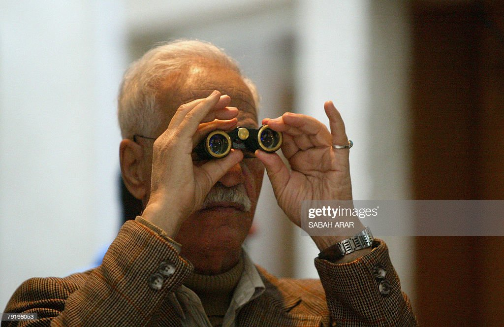 An Iraqi uses his binoculars to follow the prices of shares at the Iraqi Stock Exchange in central Baghdad, 24 January 2008. Brokers on the chaotic floor of the Iraq stock market were more concerned today with latest news on violence and bombings than with the economic factors shaking global markets.