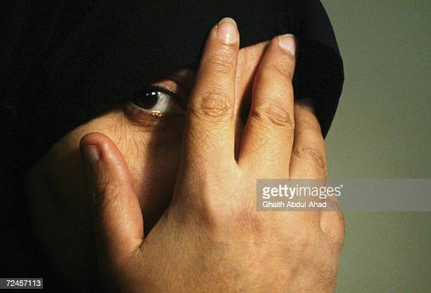 An Iraqi veiled woman covers her face with her hand March 9 2005 in Baghdad Iraq As violence and religious extremism flourishes in the Iraqi society...