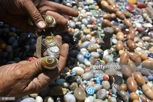 An Iraqi vendor displays semiprecious jewellery stones some of them etched with religious verses at a streetside market in Baghdad on July 11 2008 An...