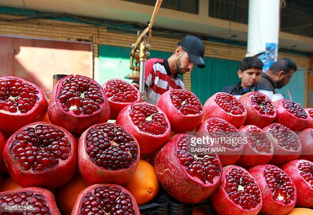 An Iraqi vendor sells freshly squeezed pomegranate juice at his stall in the capital Baghdad on November 27 2015 ARAR