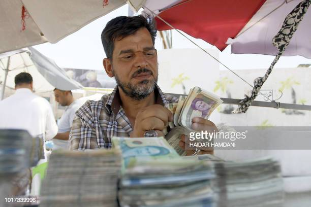 An Iraqi vendor sells Iranian currency in a street in Najaf on August 14 2018 Iraqis in the holy city of Najaf are being hit hard by US sanctions on...