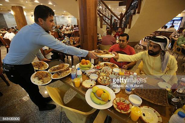 An Iraqi waiter serves customers breaking their fast with the traditional Iftar meal at a restaurant during the Muslim fasting month of Ramadan on...