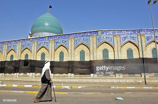 An Iraqi walks in front of Shiite alKhalani mosque in central Baghdad covered by a black shroud 23 February 2006 as the country went into a three day...