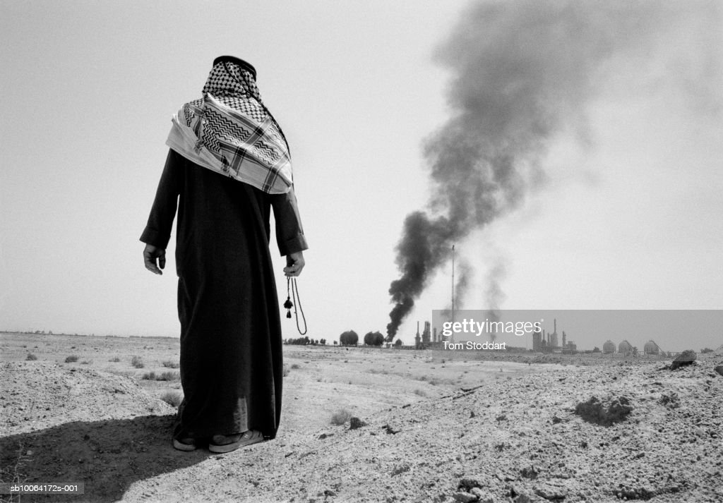 Man watching burning petrochemical plant, rear view (B&W) : News Photo