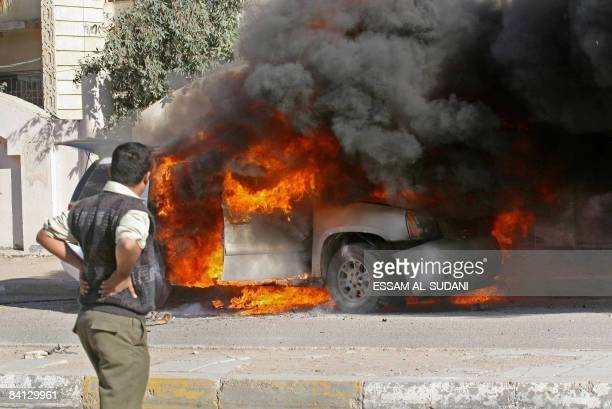 An Iraqi watches as the car of Basra Provincial Council member Bassem alMusawi of a local Shiite party burns after the detonation of a sticky bomb on...