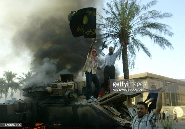 An Iraqi waves a black flag emblazoned with the name Tawhid wal Jihad the organisation of suspected AlQaeda operative Abu Mussab alZarqawi as he...