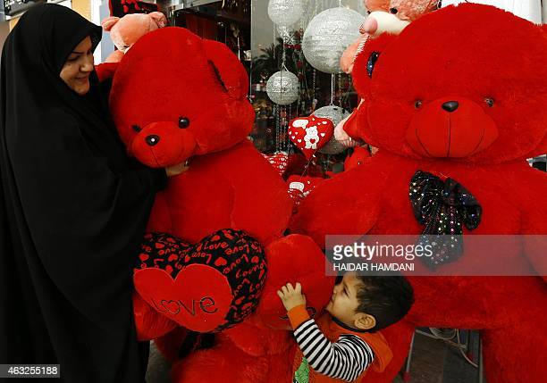An Iraqi woman and child hold a teddy bear as they shop for gifts ahead of Valentine's Day in the central Iraqi city of Najaf on February 12, 2015....