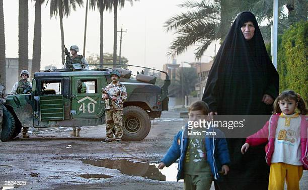 An Iraqi woman and children walk past a joint patrol of US Army First Armored Division soldiers and Iraqi Civil Defense Corps soldiers December 28...
