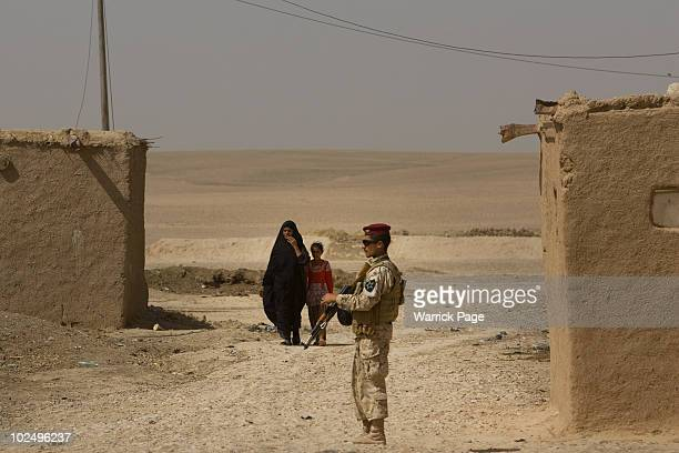 An Iraqi woman and girl walk towards a Kurdish Peshmerga soldier as US Iraq and Kurdish forces conduct a village clearance operation on June 11 2010...