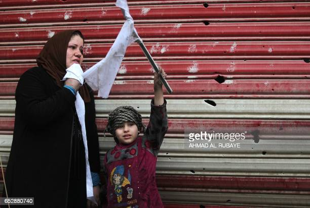 TOPSHOT An Iraqi woman and her daughter stand on a street holding white flags as Iraqi forces secure Mosul's AlDawasa neighbourhood on March 13...