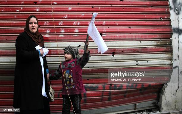 An Iraqi woman and her daughter stand on a street holding white flags as Iraqi forces secure Mosul's AlDawasa neighbourhood on March 13 during an...