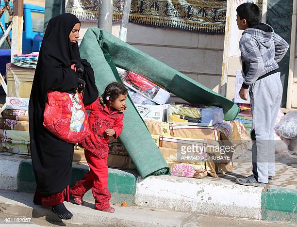 An Iraqi woman and her girl who fled Fallujah with his family walk past carpets and mattresses distributed by the International Organization for...