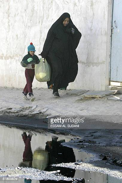 An Iraqi woman and her son walk next to a pond of oil that leaked from a nearby pipeline damaged by insurgents in alZubair some 50 kms south of the...