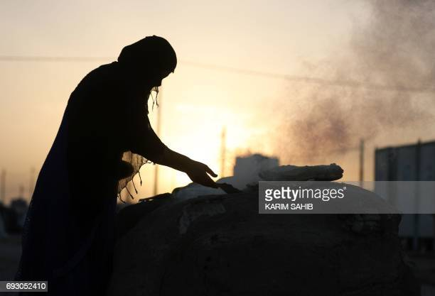 An Iraqi woman bakes bread at the AlKhazir camp for internally displaced people located between Arbil and Mosul on June 6 2017 Hundreds of thousands...