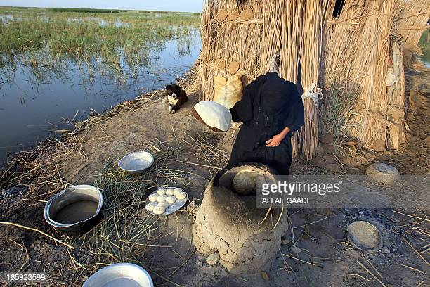 An Iraqi woman bakes bread in a traditional clay oven in the Hor or marshes near Nasiriyah 300 kilometres southeast of Baghdad on April 6 2013 The...