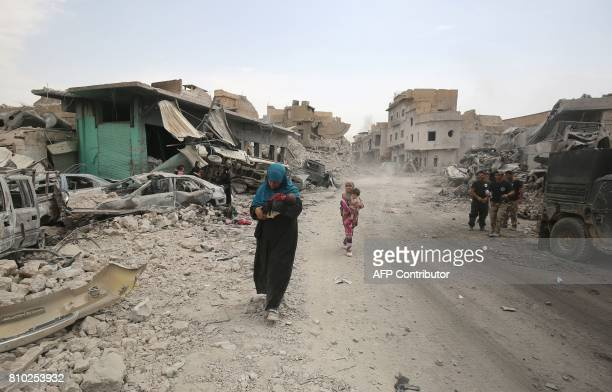 An Iraqi woman carries a child as they flee from the Old City of Mosul on July 7 during the Iraqi government forces' offensive to retake the city...