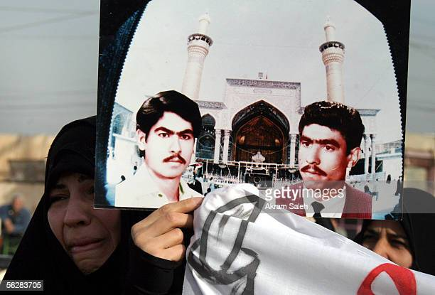 An Iraqi woman carries a picture of her brothers who were allegedly killed by Saddam Hussein's regime as they take part in a demonstration demanding...