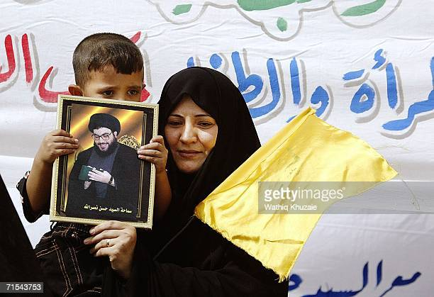 An Iraqi Woman carries her child with a picture of Lebanese militia Hezbollah leader Hassan Nasrallah as she takes part in a protest against Israel's...