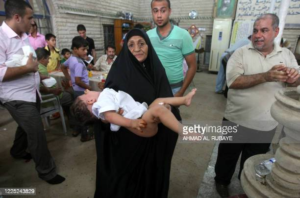 An Iraqi woman carries her son after he was circumcised in Baghdad's impoverished district of Sadr city on July 15 2011 at the start of a twoday...