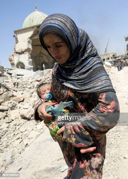 An Iraqi woman carrying an infant walks by the destroyed AlNuri Mosque as she flees from the Old City of Mosul on July 5 during the Iraqi government...