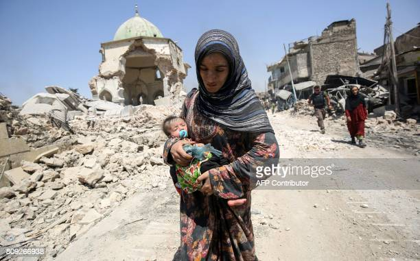 TOPSHOT An Iraqi woman carrying an infant walks by the destroyed AlNuri Mosque as she flees from the Old City of Mosul on July 5 during the Iraqi...