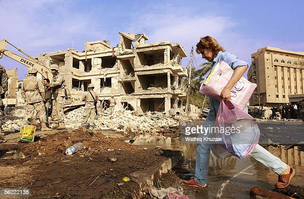 An Iraqi woman carrying her belongings in a plastic bag crosses the site where two suicide car bombs exploded near Alhamra hotel on November 18 2005...