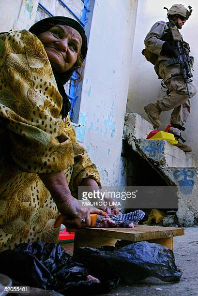 An Iraqi woman chops meat as US soldier from the 1st Battalion 24th Infantry Regiment walks down stairs inside her home during a patrol in the...