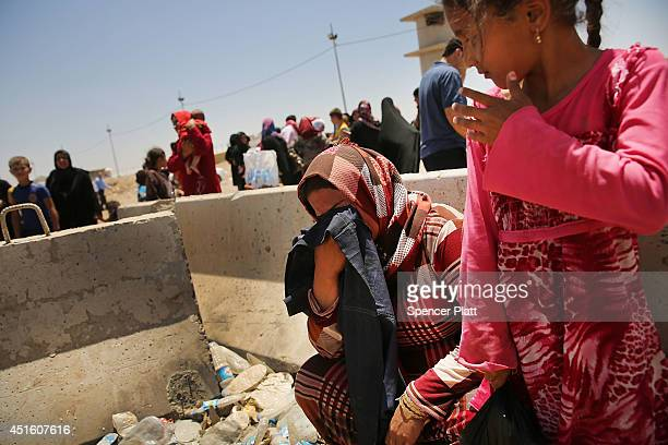 An Iraqi woman cries as her daughter looks on as Iraqis who have fled recent fighting in the cities of Mosul and Tal Afar try to enter a temporary...