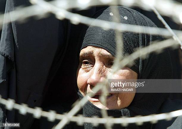 An Iraqi woman cries as she queues up with other people outside the Abu Ghraib prison 30 kms west of Baghdad 13 May 2004 waiting to have information...