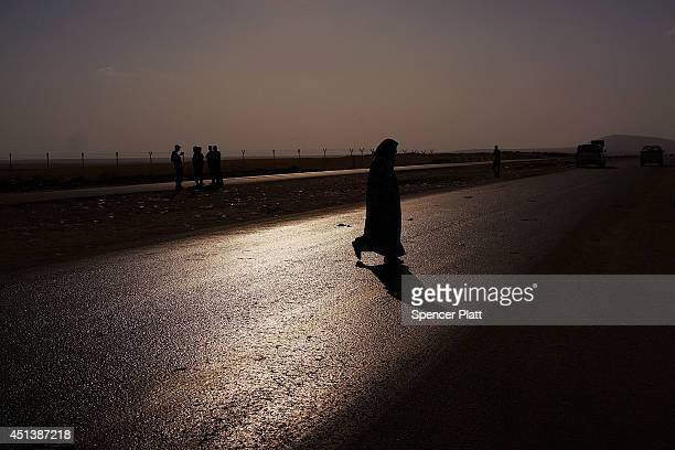 An Iraqi woman crosses a road near a displacement camp for those caughtup in the fighting in and around the city of Mosul on June 28 2014 in Khazair...