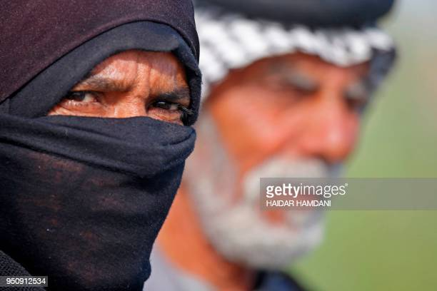 An Iraqi woman farmer looks on as she stands in a field in Diwaniyah, around 160 kilometres south of the capital Baghdad, on April 2, 2018. - Iraqi...