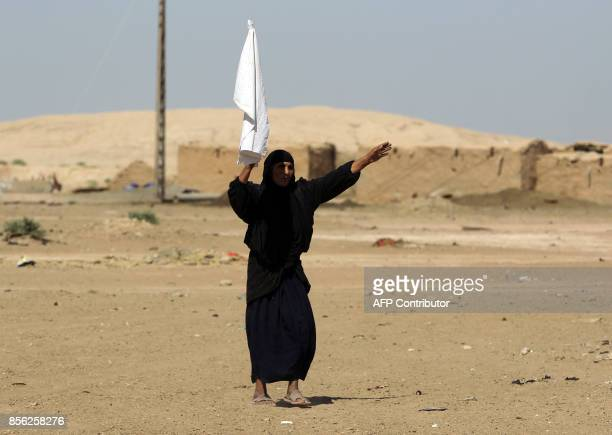 An Iraqi woman from a neighbouring village waves a white flag as Iraqi forces and fighters from the Hashed alShaabi advance towards the Islamic State...