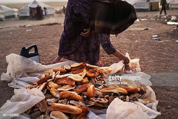 An Iraqi woman gathers bread in a temporary displacement camp for Iraqis caughtup in the fighting in and around the city of Mosul on June 24 2014 in...