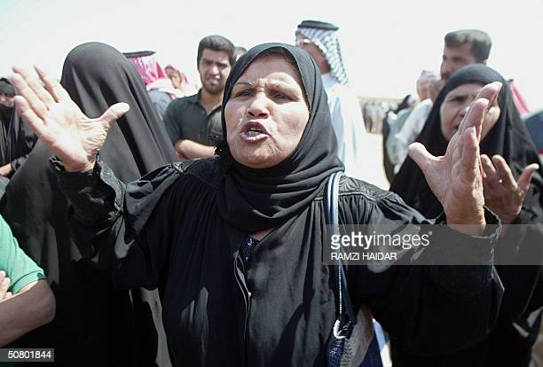 An Iraqi woman gestures as she protests at the entrance of Abu Gharib prison 05 May 2004 demanding the release of prisoners and the departure of US...