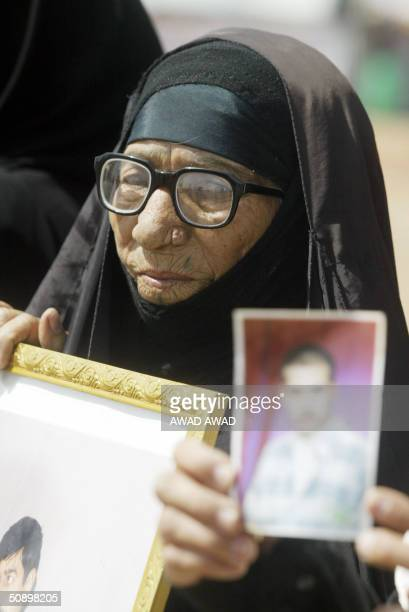 An Iraqi woman holds a picture of a relative as she and others gather on the last day of a three day sit in at Abu Ghraib prison west of Baghdad 26...
