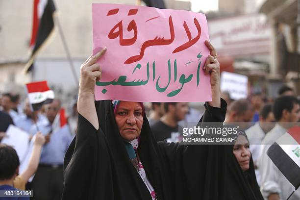 An Iraqi woman holds a placard during a demonstration against corruption and poor services on August 6 in the Shiite shrine city of Karbala south of...