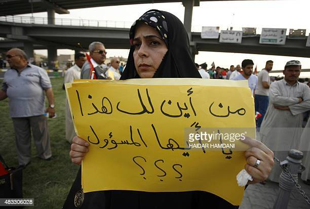 An Iraqi woman holds a placard during a demonstration against corruption and poor services on August 7 2015 in the holy city of Najaf Several...