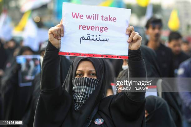 TOPSHOT An Iraqi woman holds a placard during the funeral of Iranian military commander Qasem Soleimani Iraqi paramilitary chief Abu Mahdi alMuhandis...