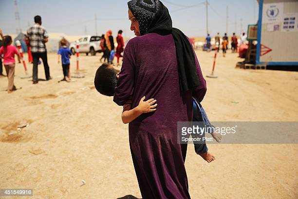 An Iraqi woman holds her exhausted son as over 1000 Iraqis who have fled fighting in and around the city of Mosul and Tal Afar wait at a Kurdish...