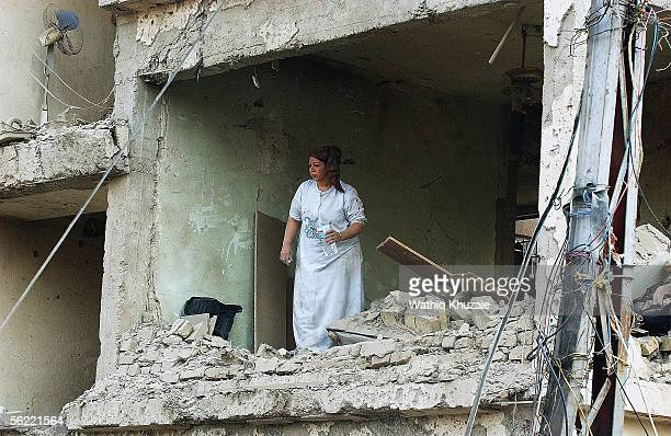 An Iraqi woman inspects her apartment in the collapsed building where two suicide car bombs exploded near an Interior Ministry building causing some...