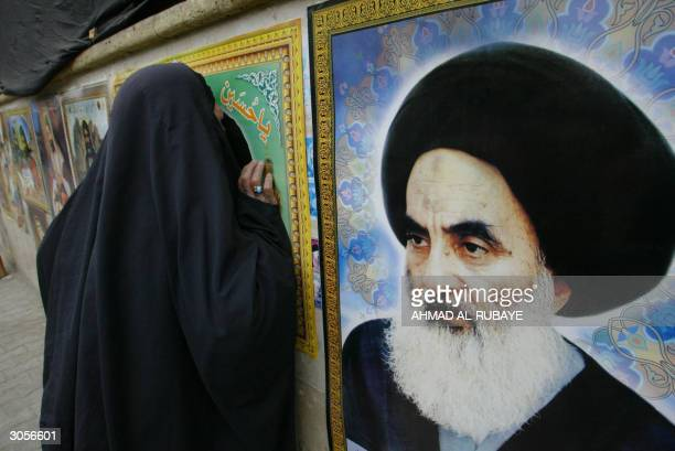 An Iraqi woman kisses a portrait of the late Ayatollah Mohammed Sadeq al-Sader, a Shiite religious leader assassinated by Saddam Hussein's deposed...