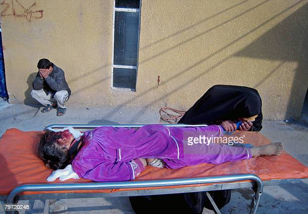 An Iraqi woman kisses the foot of her dead daughter outside the morgue of a hospital in the restive city of Baquba northeast of Baghdad on February...