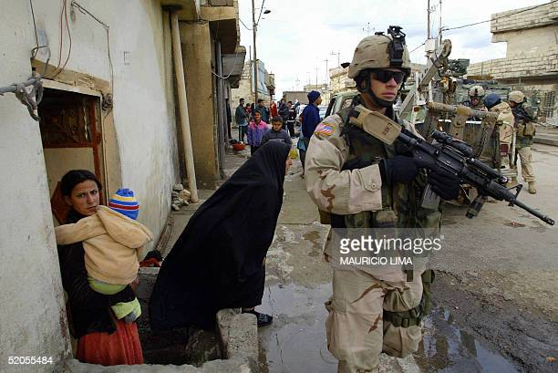 An Iraqi woman leaves her home as US soldiers from the 1st Battalion 24th Infantry Regiment walk in the street during a patrol at under privileged...